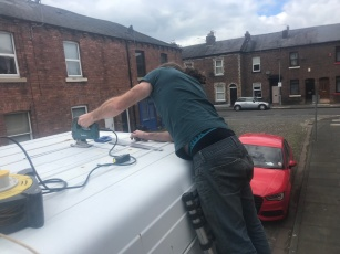 cutting a hole for the roof vent on the van